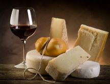 Different type of cheese and a glass of red wine