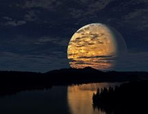 Big yellow moon reflected in river water