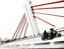 Motorcycles race on a bridge