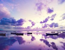 Abstract purple sky and boats on a lake