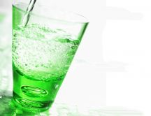 Fresh mineral water in a glass - green light