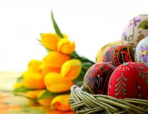 Easter egg and yellow tulips on the background