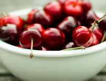Shiny cherries in a white bowl - prepare for a movie