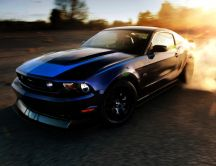 Blue Ford Mustang drifting at sunset
