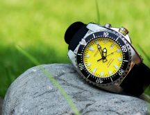 A watch in black and yellow on a stone