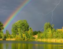 Rainbow and lightning on the dark sky