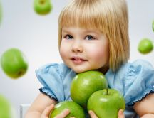 A sweet girl in blue with many green apples in her arms