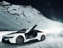 A white BMW I8 on the mountains with snow