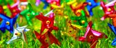 Colourful paper vanes in the green grass of spring