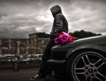 Romantic man waiting the perfect girl with flowers-Black car