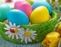 Green basket with colorful Easter eggs and a little ladybug
