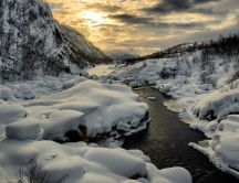 Warm sunset over the cold mountain river - Winter season
