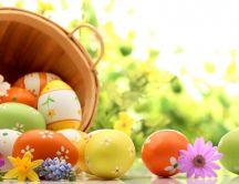 Wooden basket full with colorful Easter eggs - Spring season