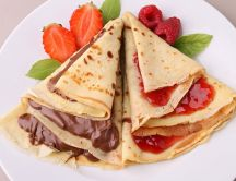 Delicious pancakes with chocolate and strawberry jam