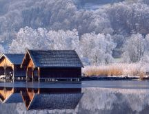 Two wooden house on the lake -View in the mirror winter time