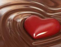 Red chocolate heart in a delicious milk chocolate bath