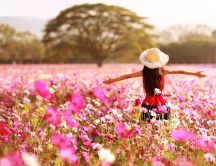 Happy girl in a field full with pink flowers - Spring season